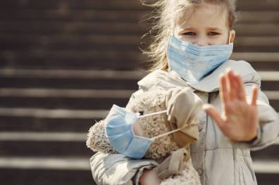 serious girl in protective mask holding plush toy in mask and showing palm against steps